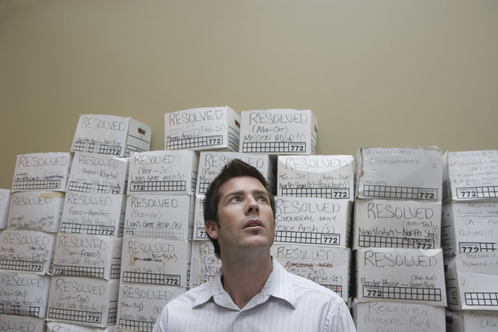Business man standing in front of stack of filing boxes in cluttered office