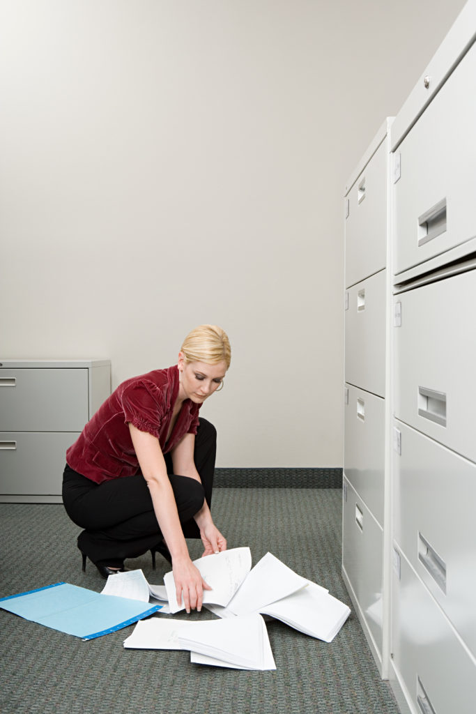 Woman picking up dropped paper